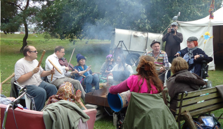 A group of diverse people sitting around a campfire, with smoke flowing, they are singing and making music.