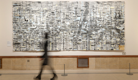 A black shadowy impression of a woman walks past a large wall, on the wall is a large painting in monochrome, white, greys and black, almost like a woven irregular pattern,as though marking changes in frequency.