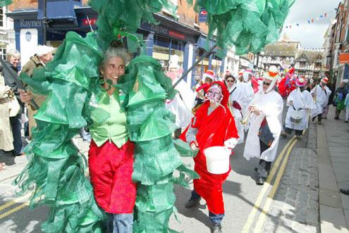 People dressed in carnival costumes parade through the streets of Ludlow. The lead person is supporting a green man structure behinde are people dressed in red and white costumes. Photograph by: News Team International Copyright DASh