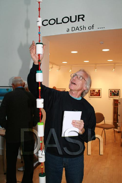 A man is standing in the middle of the image, he is reaching up to touch the artwork.  The artwork is made from plastic containers which are threaded on to thick red cord.  beads decorate the cord between the plastic containers.  the words 'Colour a DASh of' are above the open entrance to the gallery area.  Further artworks are on display in the background.  Photograph by Paula Dower copyright DASh.