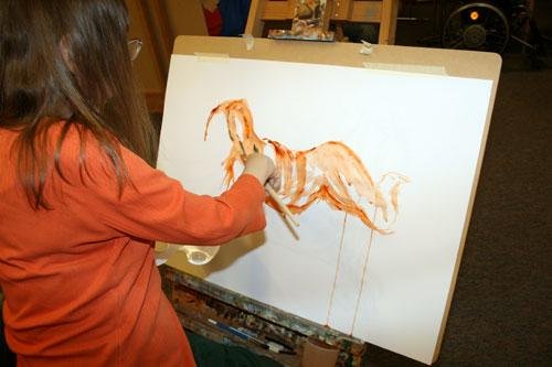 The image shows an artist painting a life drawing model, artist Caroline Cardus. The artist is working on an easel and is using orange paint on paper.  Photograph by Paula Dower copyright DASH 2010.