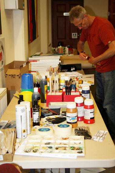 The image shows a table full of art materials, paints, paintbrushes, pencils, charcoal, palettes, canvases.  Artist Fran O'Boyle is getting some paint.  Photograph by Paula Dower copyright DASH 2010.