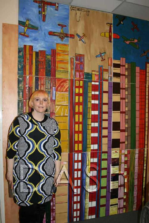 Barriers Artist, Rowena Keaveny stands next to her collaborative painting.  The painting consists of nine separate canvases, which make a block - 3 tall and 3 high.  The painting uses all colours and shows tower blocks on the bottom two rows, on the top row is the top of the tower block and in the sky above are airplanes.  The canvases were all painted by artists involved in the Barriers project.  Photograph by Paula Dower copyright DASh.