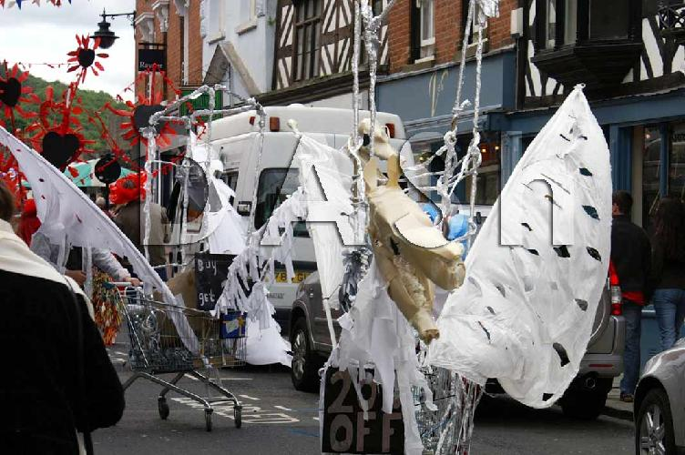 The photograph show two carnival 'horses'.  The horses are made from shopping trolleys.  They have wings of white material and the heads are made from foam.  The photograh was taken on the High St there are buildings and cars behind the 'horse'.  Photograph copyright Ian Wainwright.