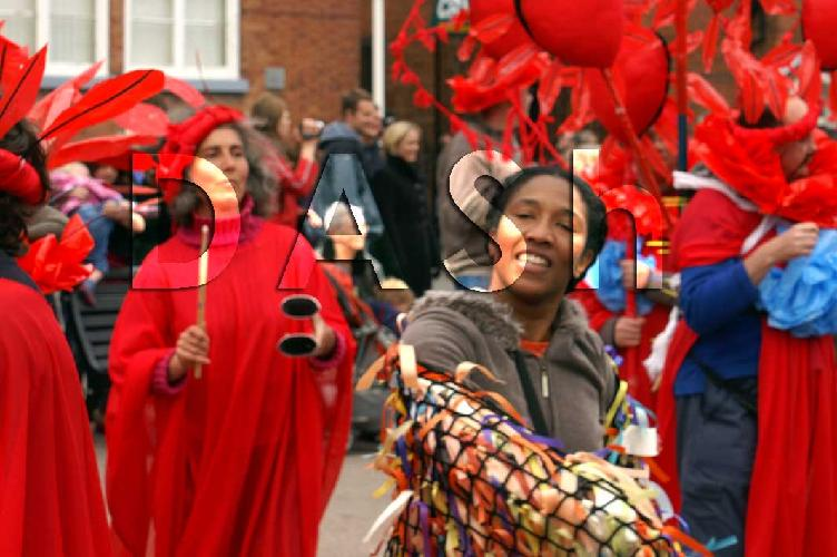 Trinidadian Carnival Artist Mary Ann Roberts is in the foreground of the picture, she wore the clown coat, which was net with multicoloured ribbons tied to it.  In the background are members of the band who are dressed in red gowns with red feather headresses.  Photograph copyright Ian Wainwright.