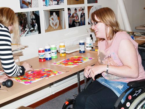 The image shows Cheryl, who is a wheelchair user, and Rachel experimenting with paint making random shapes using red, green, orange, blue, pink, and yellow Behind them on a table are containers of paint.  Photograph by Paula Dower, copyright DASH 2010