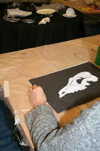 The photograph shows a painting of a animal skull in the foreground and a table with the skull and other objects on in the background. copyright DASH 2010