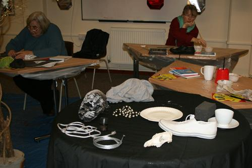 The December visusal arts workshop focussed on light and shade.  The photograph shows participants painting in the background and a table in the foreground with a black cloth with various objects such as cloth, beads, a training pump, a cup and saucer. copyright DASH 2010