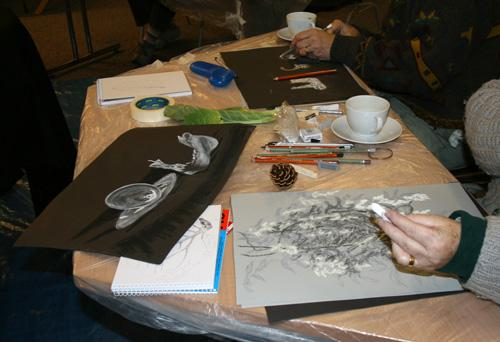 The photograph shows a artists drawing with chalks on a table. One drawing shows a cup and saucer and a skull, the artist in the foreground is drawing foliage.  All the drawings use black, white and shades of grey.  copyright DASH 2010
