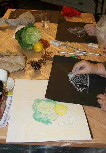 The photograph shows a artists drawing at a table. They are both drawing a white fish on black paper.  Also on the table are a cabbage, lemon and a fir cone.  Another drawing is of the cabbage and lemon.  copyright DASH 2010