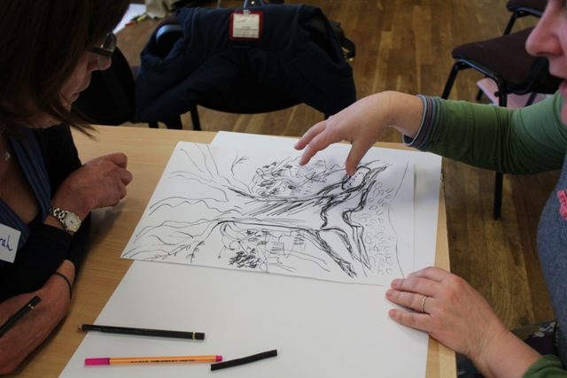 Two participants discussing a drawing produced at the workshop