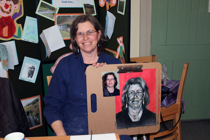 An artist with completed canvas at end of portrait painting workshop