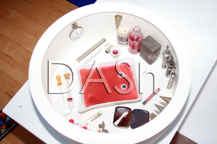 The image shows one of Jenny Brown's artworks.  A circular white container has medical paraphernalia displayed inside, included are: pipettes, syringes, bandages, a watch, a rectangular specimen dish is filled with red liquid and two blue eyes!  Original artwork Jenny Brown, Photograph by Paula Dower copyright DASh.