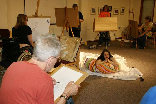 The image shows a group of artists, disabled and non-disabled, drawing and painting a life model.  Photograph by Paula Dower copyright DASH 2010.