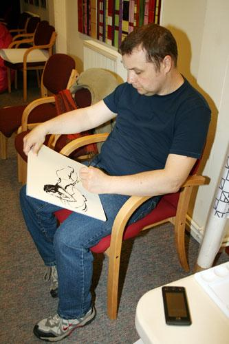 The image shows artist Neil Webber and his painting of the life model.  Neil is sitting on a chair and is using black ink on a pad of paper.  Photograph by Paula Dower copyright DASH 2010.