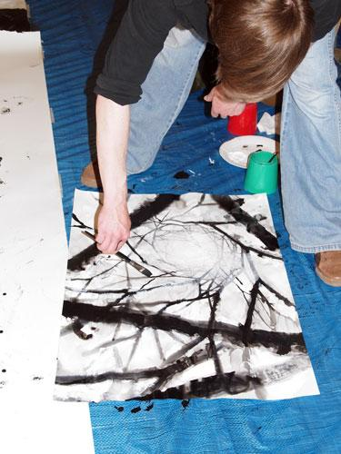 The image shows the artist working with black ink on a large sheet of white paper.  He is painting a series of black lines of varying widths, which are wider on the outside, the lines form a kind of spider's web.  Photograph by Paula Dower, copyright DASH 2010.