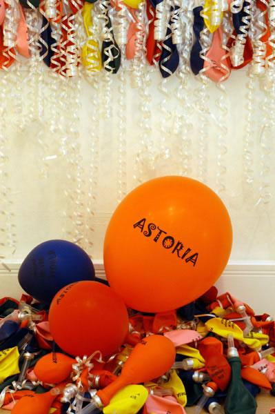 multicoloured ballons with Astoria printed on, white corkscrews of streamers, photo by Anthea Bevan