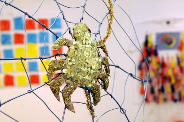 gold spider made with sequins and glitter, sitting on web of metal wire, photo by Anthea Bevan