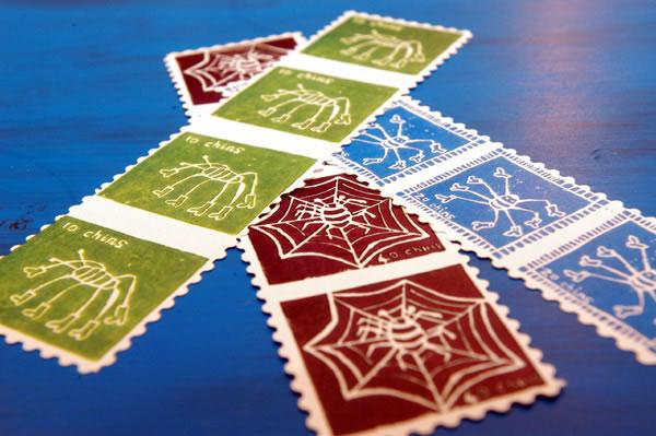 Astoria stamps - red, green and blue stamps with white outlines of spiders, currency cost is in chins, photo by Anthea Bevan