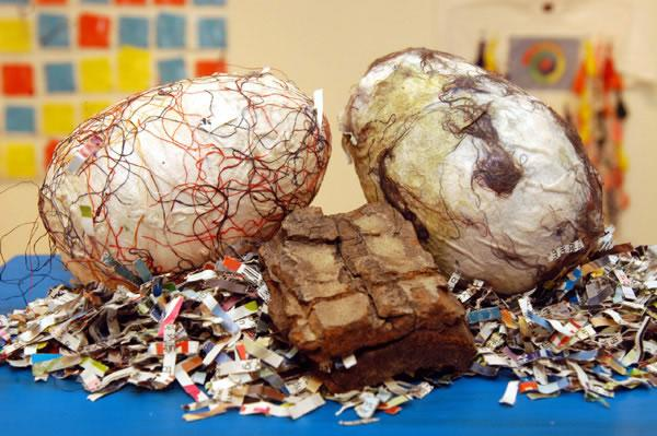 Three Astorian dinosaur eggs, the eggs are made of paper and textiles, they sit on top of shredded paper.