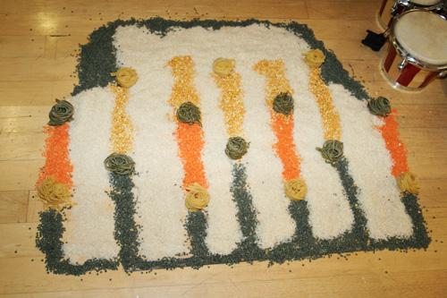 Rangoli image created with rice, pasta and lentils.  The form is abstract using lines of green orange and yellow lentils, blocked in with white rice and rolls of linguini. Photograph by Paula Dower copyright DASh